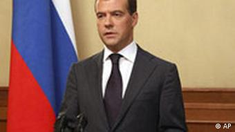 Medvedev in front of a Russian flag