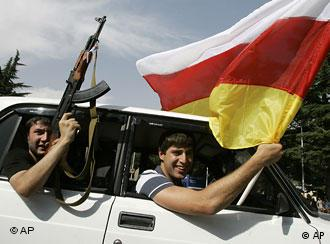 South Ossetian separatist fighters wave a Kalashnikov in Tskhinvali