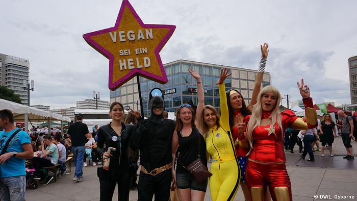 People dressed as superheroes hold a star-shaped sign saying, Vegan: Be a hero (DW/L. Osborne)