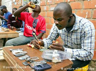 A man repairing a cell phone at a market in Abuja
