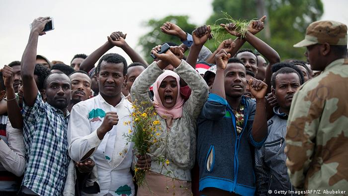 Oromo protesters crooss their wrists above their heads as a sign of ptotest against the government, while a soldier look on