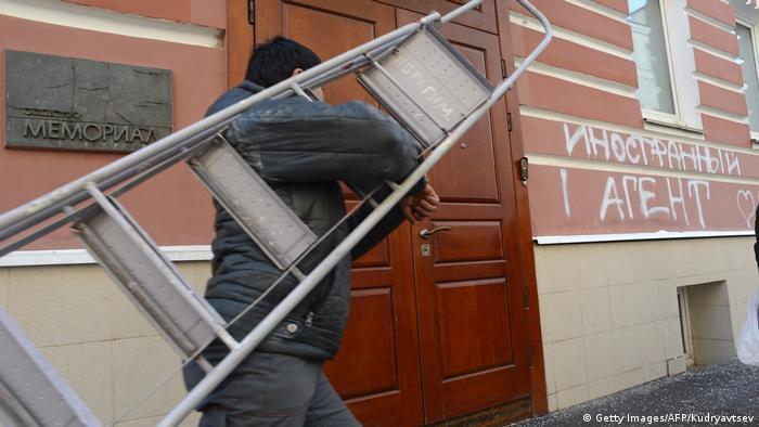Мужчина с лестницей у офиса Мемориала