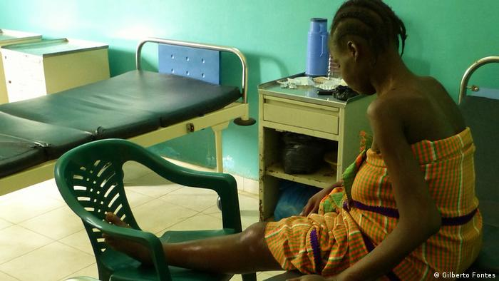 A woman patient sits on a bed in Bissau