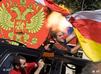 South Ossetian separatist fighters fire Kalashnikovs and wave their white-yellow-red flag while riding in a car