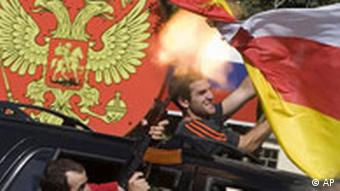 South Ossetian separatist fighters fire Kalashnikovs and wave their white-yellow-red flag while riding in a car in Tskhinvali, the capital of Georgia's separatist-controlled territory of South Ossetia