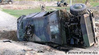 Overturned armoured vehicle that has been subject to bomb attack