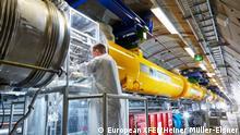 DE: Mit einem kleinen Mobil-Reinraum stellen Techniker die Verbindungen zwischen zwei Beschleunigermodule im Tunnel her. Diese Verbindungen versorgen die Module mit flüssigem Helium, um die supraleitenden Hohlraumresonatoren auf eine Temperatur von -271°C zu kühlen. (c) European XFEL/Heiner Müller-Elsner