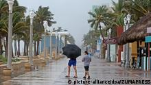 October 6, 2016 - Hollywood, FL, USA - Pedestrians walk on the Hollywood Beach boardwalk as the wind and rains begin from Hurricane Matthew on Oct. 6, 2016 in Hollywood, Calif |