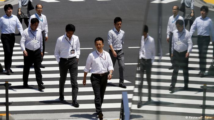 Trabalhadores japoneses atravessam rua em Tóquio