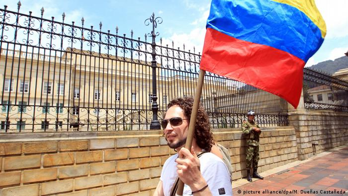 Kolumbien - Mann trägt Kolumbianische Flagge (picture alliance/dpa/M. Dueñas Castañeda)