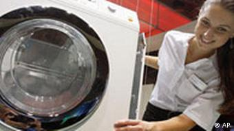An employee of a household appliance company poses at a fragmented washing machine two days ahead of the official opening of the consumer electronics fair 'IFA 2008' in Berlin, Germany, Wednesday, Aug. 27, 2008.