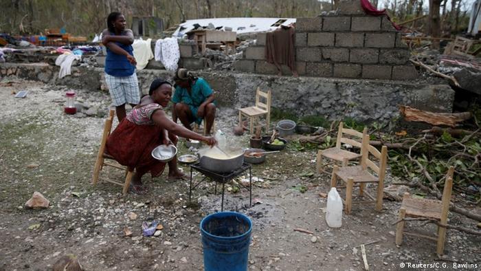 Eine Frau kocht im Freien vor einem zerstörten Gebäude (Foto: Reuters)