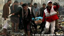 Yemeni rescue workers carry a victim on a stretcher amid the rubble of a destroyed building following reported airstrikes by Saudi-led coalition air-planes on the capital Sanaa on October 8, 2016. Rebels in control of Yemen's capital accused the Saudi-led coalition fighting them of killing or wounding dozens of people in air strikes on Sanaa. The insurgent-controlled news site sabanews.net said that coalition planes hit a building in the capital where people had gathered to mourn the death of an official, resulting in dozens of dead or wounded. / AFP / MOHAMMED HUWAIS (Photo credit should read MOHAMMED HUWAIS/AFP/Getty Images)