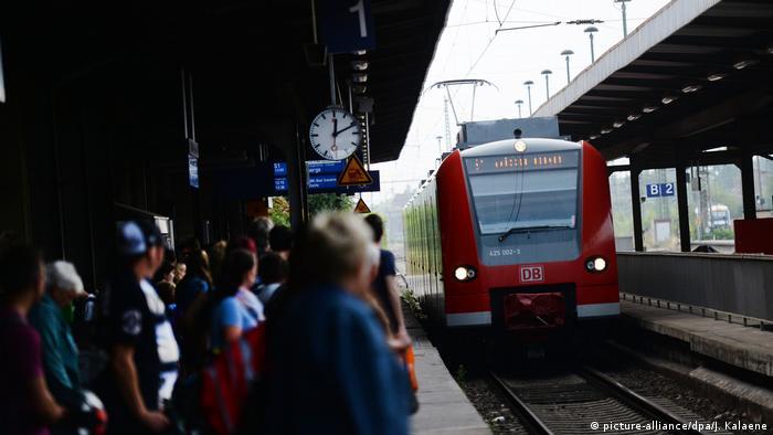 Menschen stehen am Bahnsteig und blicken in Richtung eines einfahrenden, roten Zuges. (picture-alliance/dpa/J. Kalaene)