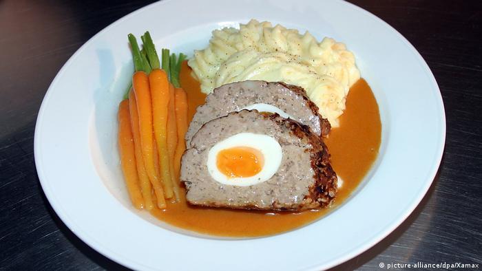Un plato con dos rebanadas de pastel de carne, puré de papas y zanahorias cocidas.