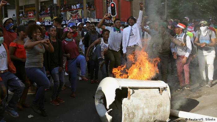 South African student protesters chanting slogans behind a burning barricade