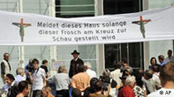 In this photo taken June 2, 2008 protesters gather outside the Museion museum in Bolzano, northern Italy near a banner saying while the frog on the cross is being shown do not enter the building referring to a sculpture portraying a green frog nailed to a cross on show inside