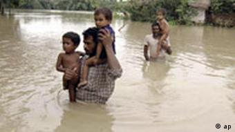 Villagers wade through flood waters in Madhepura District in Bihar state, India, Thursday, Aug. 28, 2008. The death toll from this year's monsoon has already climbed past 800 across India, and now some 1.2 million people have been marooned and about 2 million more affected in Bihar state, where the Kosi river has burst its banks, breached safety embankments and submerged all roads leading to the region. (AP Photo/Aftab Alam Siddiqui)