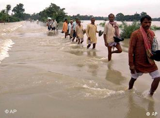 Villagers wade through floodwaters on a stretch of the National Highway 106 at Veerpur, in the northern Indian state of Bihar, Friday, Aug. 29, 2008. The Indian government has made available more than US$200 million to combat monsoon flooding in the country's north that Prime Minister Manmohan Singh described Thursday as a national calamity. (AP Photo/Aftab Alam Siddiqui)