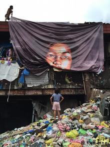 A girl watches an 'art tarp' shelter being installed in Manila's Happyland. (Kaff-eine)
