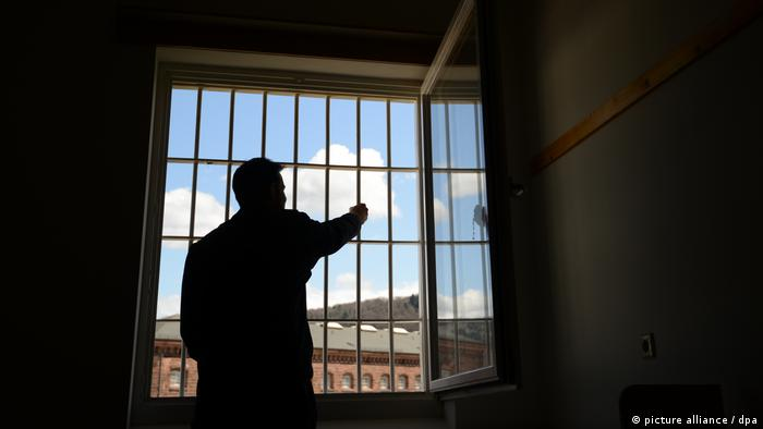 A man looking out the window at a prison in Freiburg