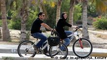 ARCHIV 2011 *** An Iranian woman and a man ride their hired bicycles in Kish Island resort in the Gulf on April 26, 2011. Iran prides itself on the natural beauties of this Gulf island, one of the top vacation destinations in the Middle East, where the Islamic republic observes its strict religious codes. AFP PHOTO/ATTA KENARE (Photo credit should read ATTA KENARE/AFP/Getty Images) Thema Frau Iran Verbot