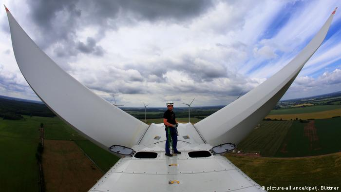 Engineer stands on top of a wind turbine
