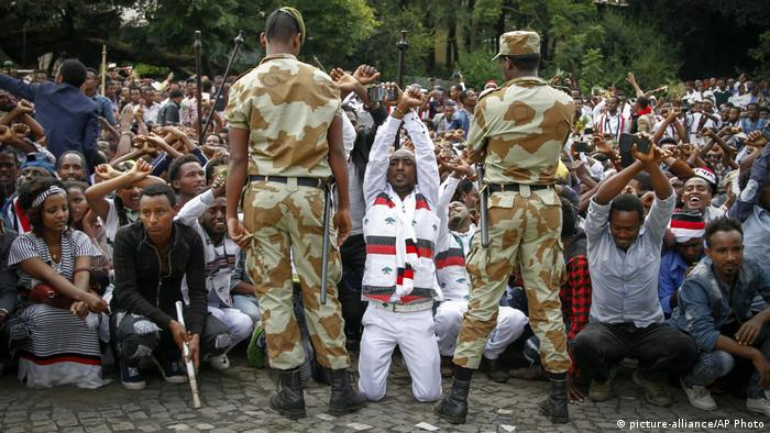 Young Oromians protesting as Ethiopian soldiers look on