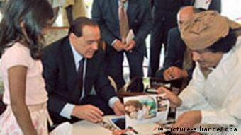 Berlusconi signing a friendship treaty with Gadhafi in 2008