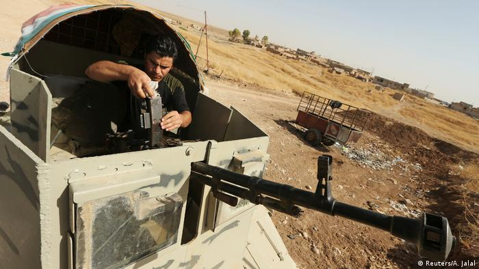 A member of the peshmerga forces takes his position with his weapon during preparations to attack Mosul