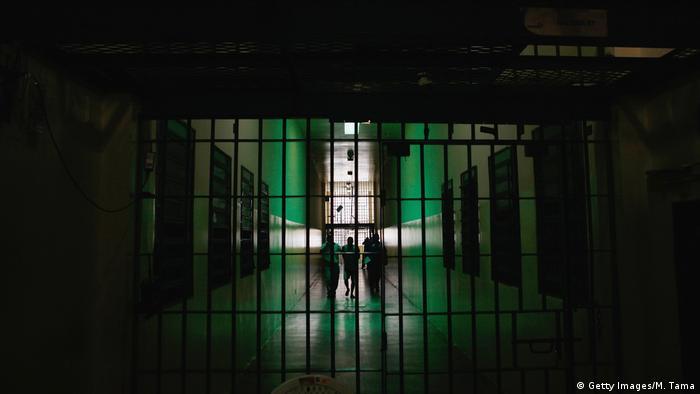 Detento anda em corredor de presídio, acompanhado de dois agentes. Ele pode ser visto atrás de uma porta gradeada.