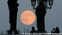 Archiv 2014 ++ People take photos as a perigee moon also known as a supermoon rises above in Skopje, Macedonia, Sunday, Aug. 10, 2014. The phenomenon, which scientists call a perigee moon, occurs when the moon in its elliptical orbit is relatively close to Earth and seen from the Earth near the horizon, appears larger and brighter than other full moons. (AP Photo/Boris Grdanoski) |