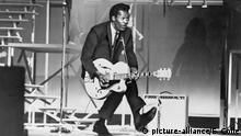 Chuck Berry (b. 1926) on stage, playing guitar. 1965.   Keine Weitergabe an Wiederverkäufer.