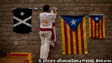 September 10, 2016 - Barcelona, Catalonia, Spain - A man hangs estelades or Catalan independentist flags on a wall downtown Barcelona the day before the celebration of the National Day of Catalonia or 'La Diada,' held on the 11th |