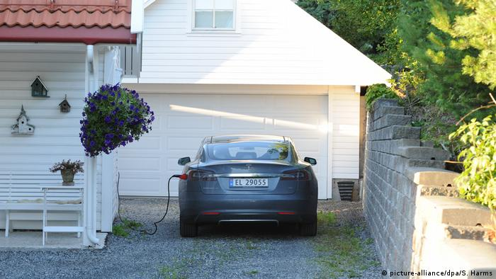 A car is in a driveway being electrically charged