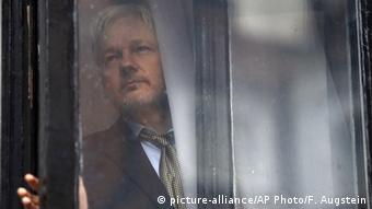 Assange appears at the window of the Ecuadorian Embassy (picture-alliance/AP Photo/F. Augstein)