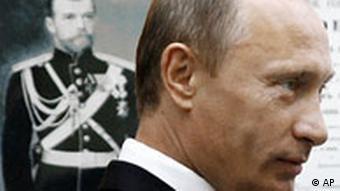 Vladimir Putin stands by a portrait of Tsar Nicholas II