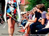 fashion catwalk with model walking down isle in a bright geometric mini-dress