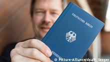"""Joachim Widera, miembro de los """"Ciudadanos del Reich"""", muestra orgulloso su pasaporte."""