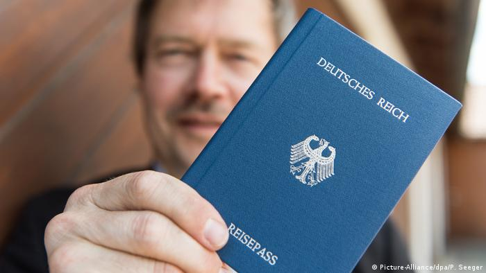 A Reichsbürger poses with his German Reich passport
