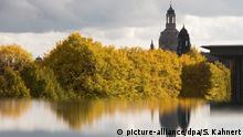Die Frauenkirche spiegelt sich am 19.10.2016 in Dresden (Sachsen) hinter herbstlich gefärbten Bäumen in einer Pfütze. Foto: Sebastian Kahnert/dpa +++(c) dpa - Bildfunk+++