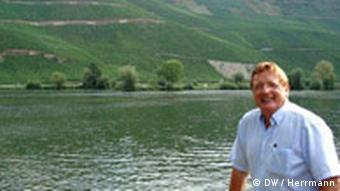 Raimund Pruem stands by the Moselle River and fields of his vines