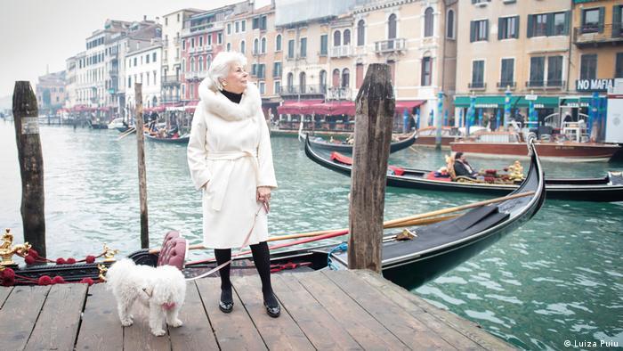 Женщина с собакой на поводке на берегу канала