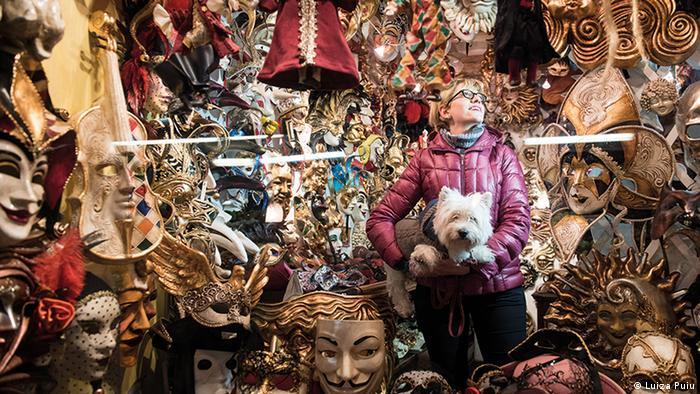 Женщина с собакой на руках на фоне итальянских масок