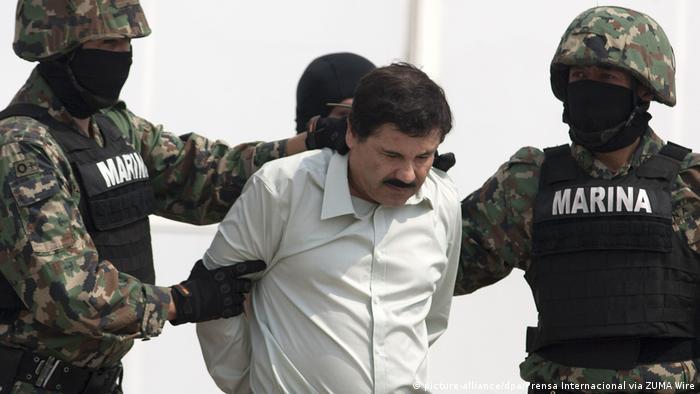 Мексиканские морские пехотинцы в черных масках ведут арестованного наркобарона Коротышку