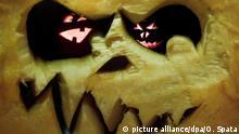 Zwei geschnitzte Halloweenkürbisse werden am 28.10.2014 in Hannover (Niedersachsen) mit Kerzen von innen beleuchtet (aufgenommen durch das Innere eines geschnitzten Kürbisses). Die amerikanische Halloween-Tradition, im Oktober Kürbisse zum Herstellen von Fratzen zu nutzen, hat sich auch in Deutschland durchgesetzt. Das Halloween-Fest, welches traditionell in der Nacht vom 31. Oktober zum 01. November gefeiert wird, geht auf einen keltischen Brauch zurück. Mit gruseligen Masken sollten zum Beginn der dunklen Jahreszeit böse Geister vertrieben werden. Foto: Ole Spata/dpa +++(c) dpa - Bildfunk+++   Verwendung weltweit
