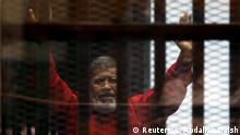 Archiv 2015 Egypt's deposed president Mohamed Mursi greets his lawyers and people from behind bars at a court wearing the red uniform of a prisoner sentenced to death, during his court appearance with Muslim Brotherhood members on the outskirts of Cairo, Egypt, June 21, 2015. REUTERS/Amr Abdallah Dalsh/File Photo