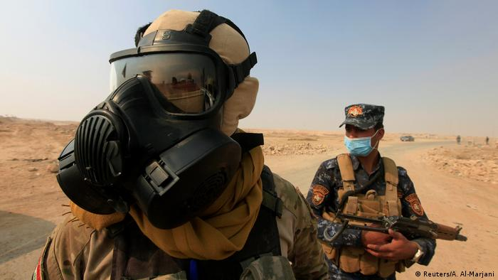 Iraqi forces wear protective masks after winds brought fumes from a nearby sulfur plant (Reuters/A. Al-Marjani)