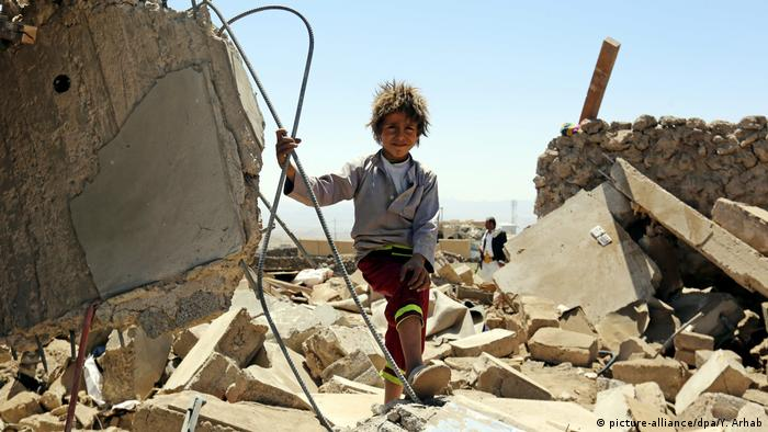 A Yemeni child stands over the rubble of a destroyed house