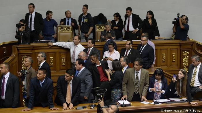 The president of the Venezuelan National Assembly, Henry Ramos Allup (C-up) observes as supporters of Venezuelan President Nicolas Maduro force their way to the National Assembly